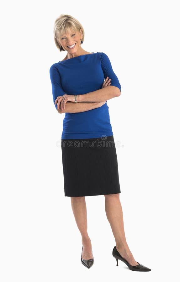Mulher de negócios feliz Standing Arms Crossed sobre o fundo branco imagem de stock royalty free