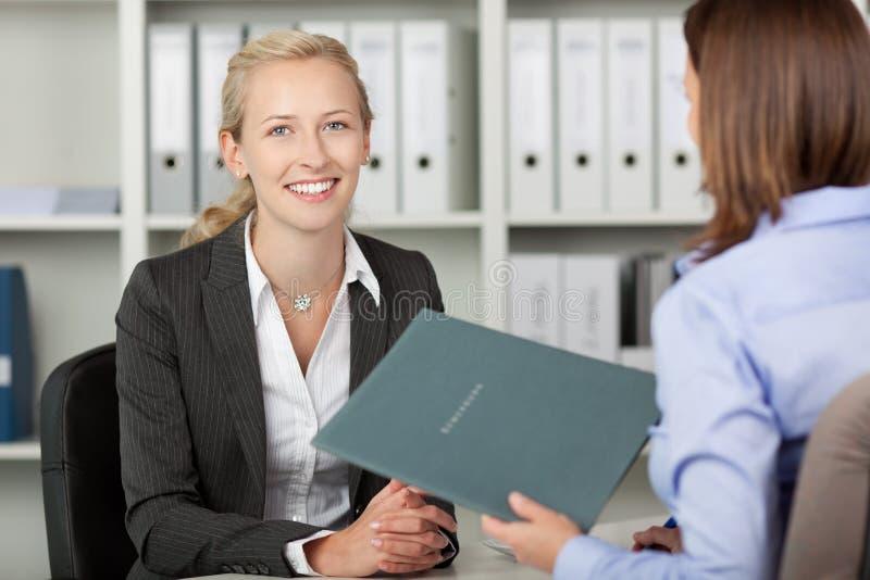Mulher de negócios With Female Candidate no escritório imagens de stock royalty free