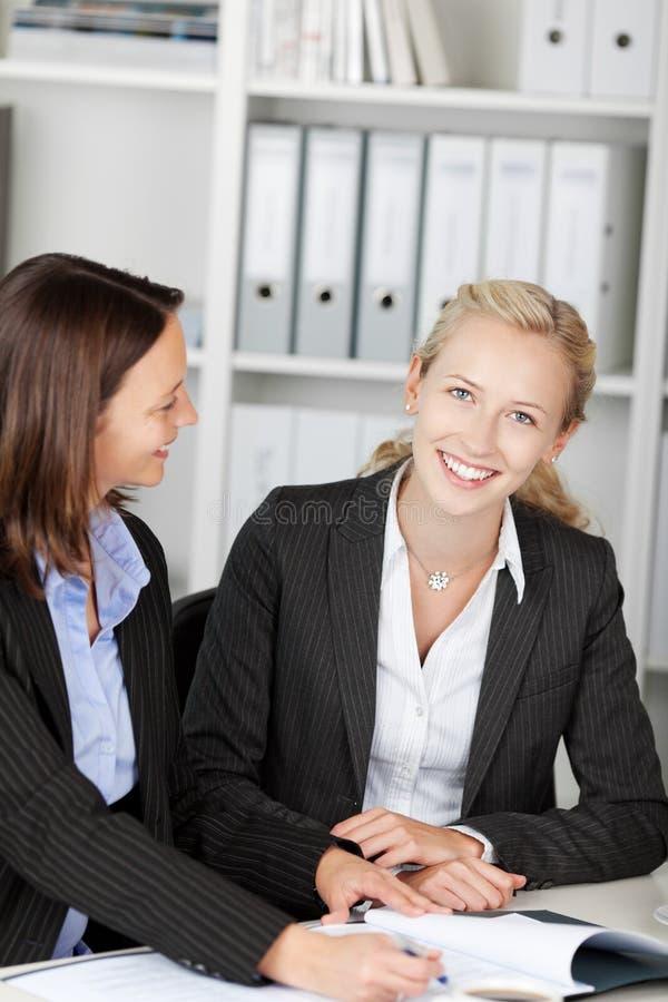 Mulher de negócios With Female Coworker na mesa fotografia de stock