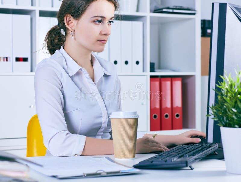 Mulher de negócios focalizada que trabalha na mesa no escritório criativo imagem de stock royalty free