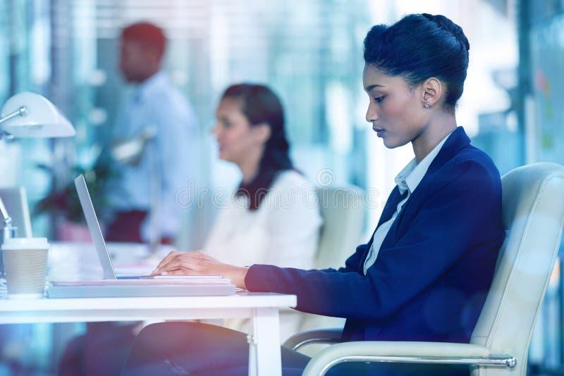 Mulher de negócios focalizada que trabalha no portátil imagens de stock royalty free