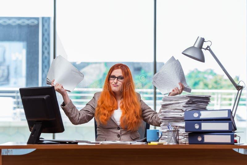 A mulher de negócios forçada com a pilha de papéis foto de stock