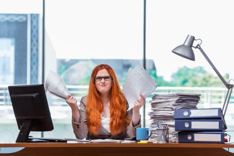 A mulher de negócios forçada com a pilha de papéis imagens de stock royalty free