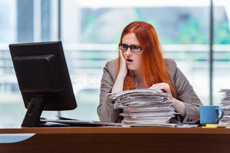 A mulher de negócios forçada com a pilha de papéis imagem de stock