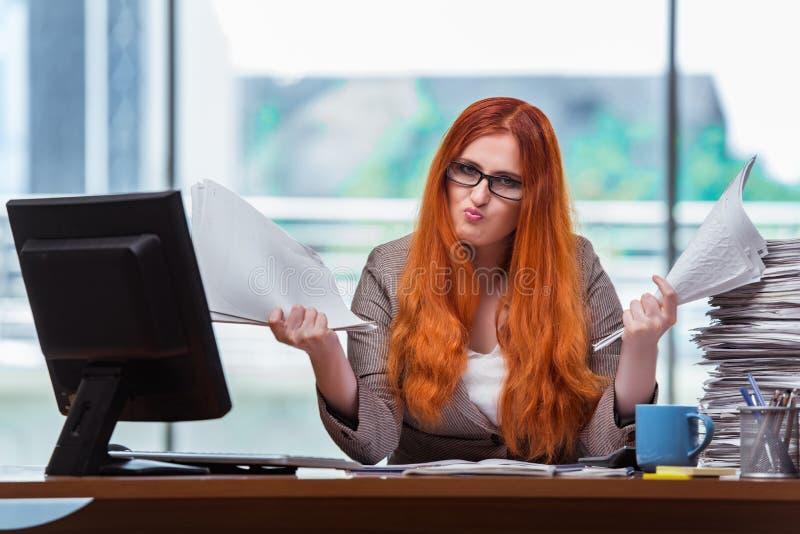 A mulher de negócios forçada com a pilha de papéis fotografia de stock royalty free
