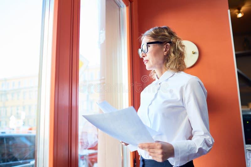 Mulher de negócios formal com o papel que olha na janela imagem de stock