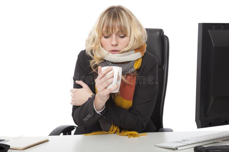 Mulher de negócios fria que bebe uma caneca de café quente fotografia de stock royalty free