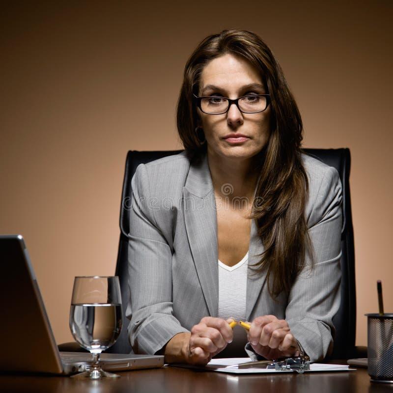 Mulher de negócios frustrante que trabalha tarde na mesa foto de stock