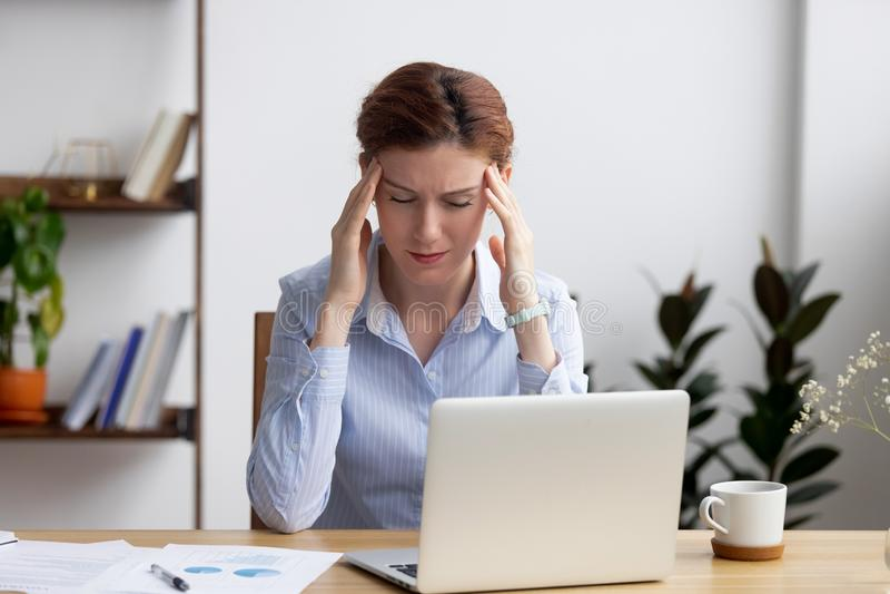 Mulher de negócios frustrante Tired que lida com o ataque forte da dor de cabeça no local de trabalho fotos de stock