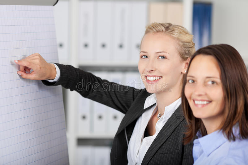 Mulher de negócios Giving Presentation While que está com colega de trabalho fotografia de stock