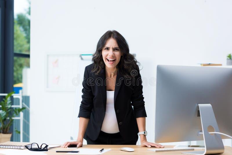 mulher de negócios grávida irritada que grita ao olhar a câmera imagens de stock