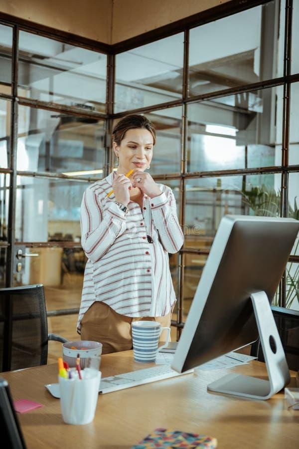 Mulher de negócios grávida nova que trabalha no escritório moderno fotografia de stock royalty free