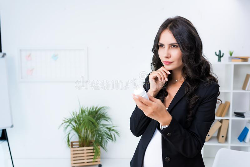 mulher de negócios grávida pensativa com o frasco dos comprimidos imagens de stock