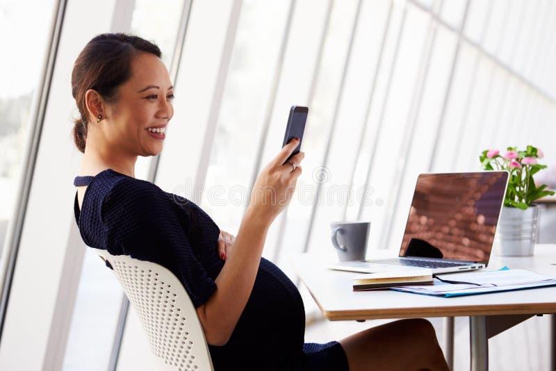 Mulher de negócios grávida Reading Text Message no escritório fotos de stock royalty free