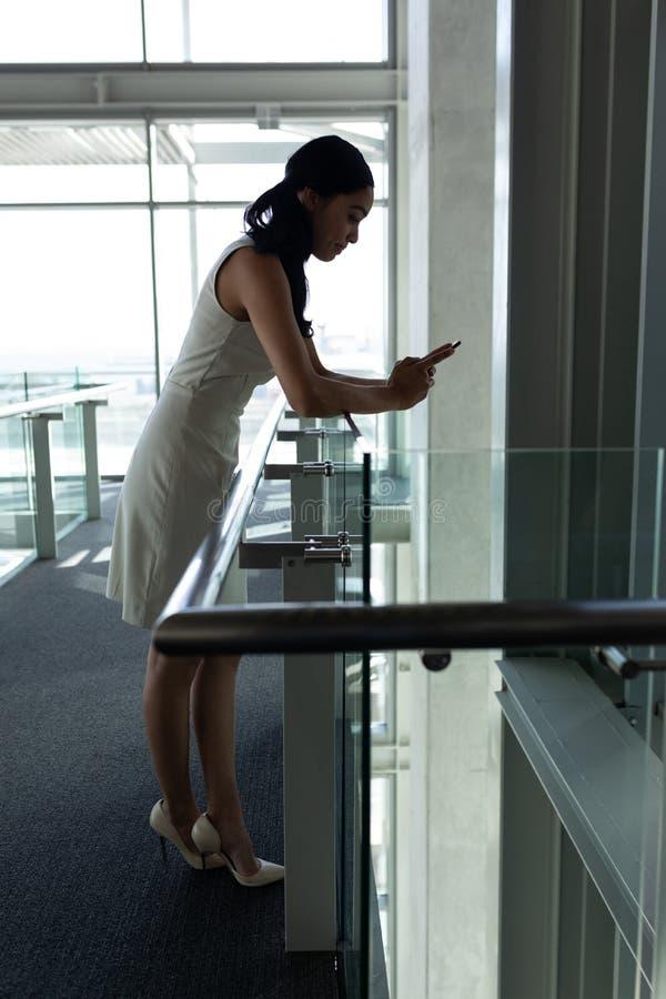 A mulher de negócios inclinou-se nos trilhos e em chating em seu telefone celular na passagem do primeiro andar fotos de stock