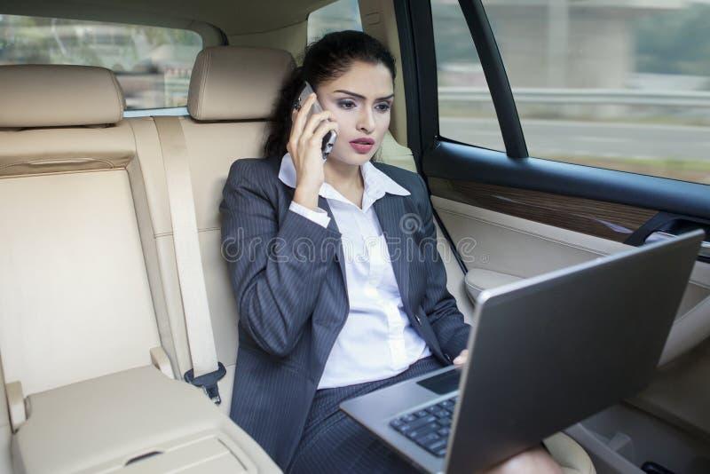 Mulher de negócios indiana ocupada que trabalha no carro fotos de stock royalty free