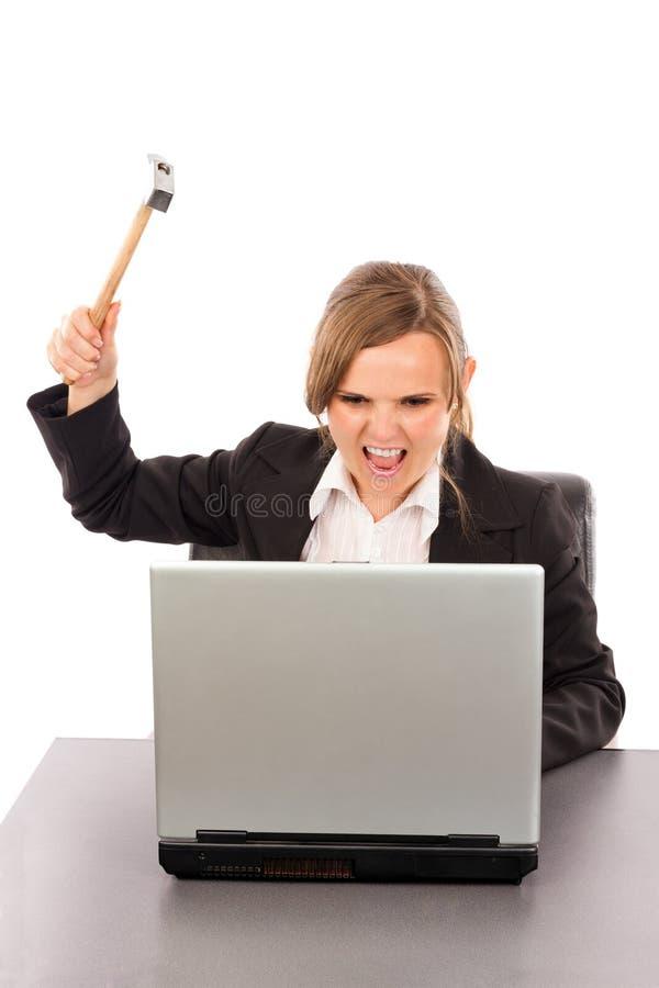 Mulher de negócios irritada com um martelo pronto para despedaçar seu whil do portátil fotos de stock