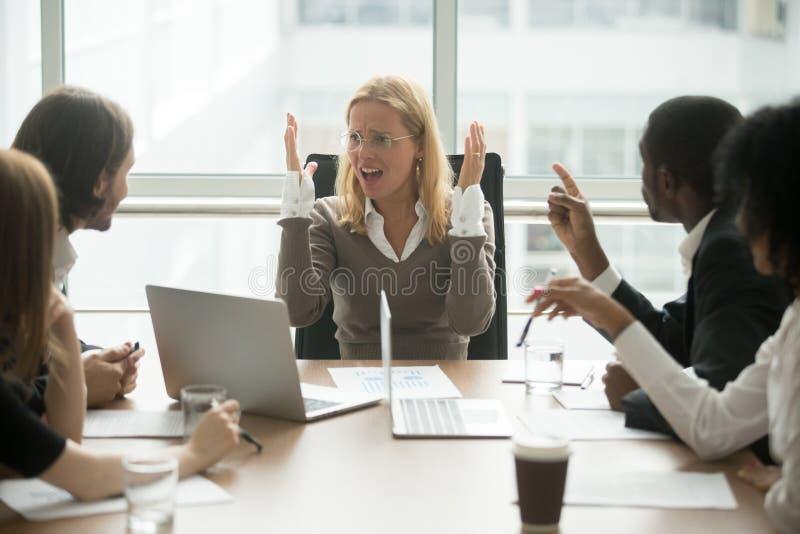 Mulher de negócios irritada forçada que discute na reunião com o collea masculino foto de stock royalty free