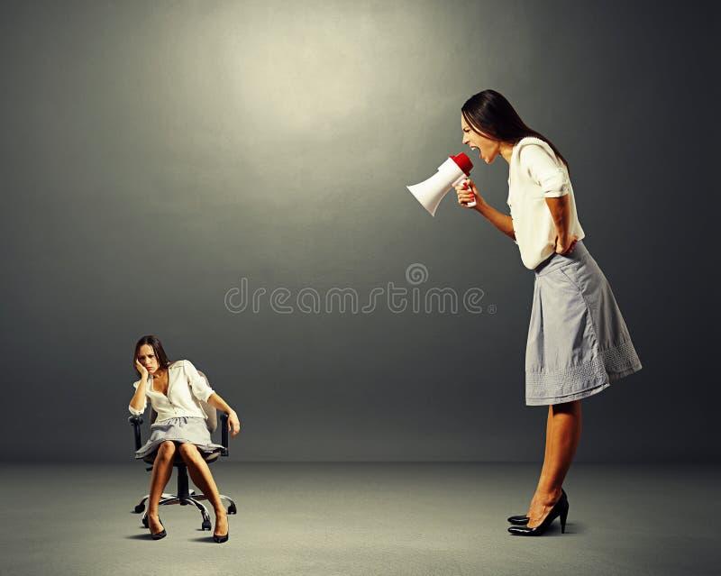 Mulher de negócios irritada que grita na mulher preguiçosa imagem de stock