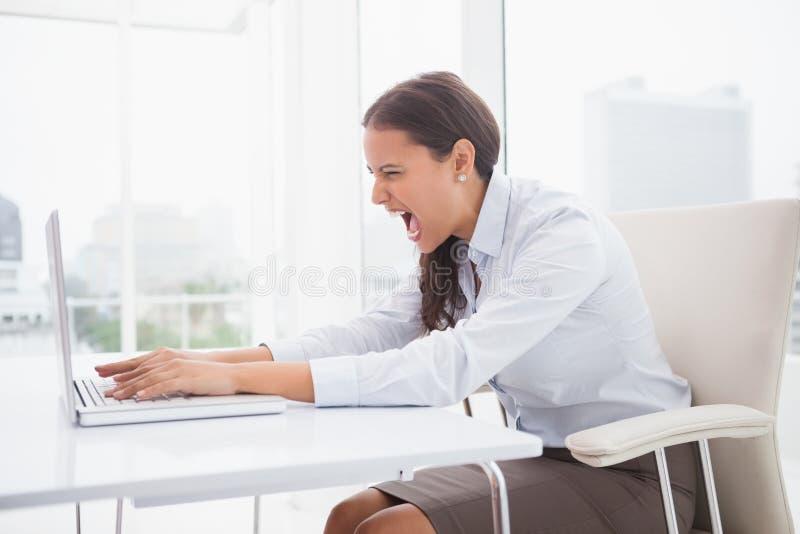 Mulher de negócios irritada que usa o portátil na mesa imagens de stock royalty free