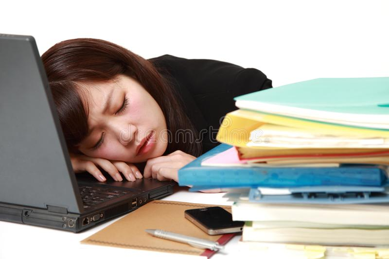 Mulher de negócios japonesa nova que dorme na mesa fotografia de stock