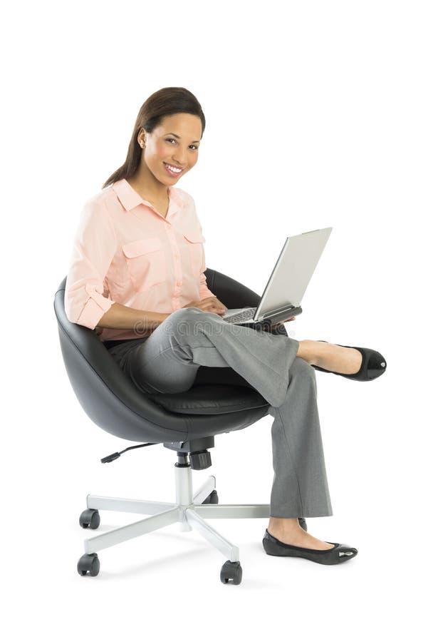 Mulher de negócios With Laptop Sitting na cadeira do escritório imagens de stock royalty free