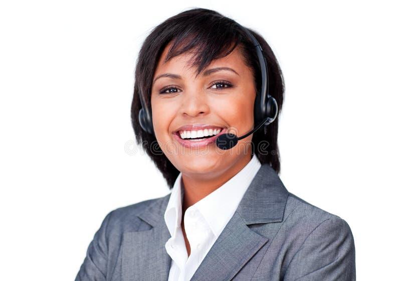 Mulher de negócios latino-americano de sorriso com auriculares sobre fotografia de stock