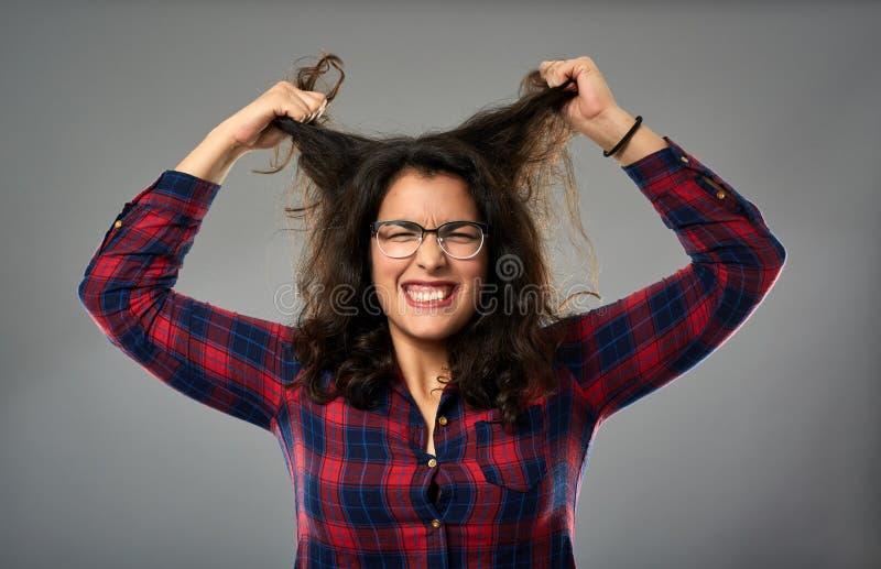 Mulher de negócios latino-americano louca que puxa seu cabelo imagem de stock