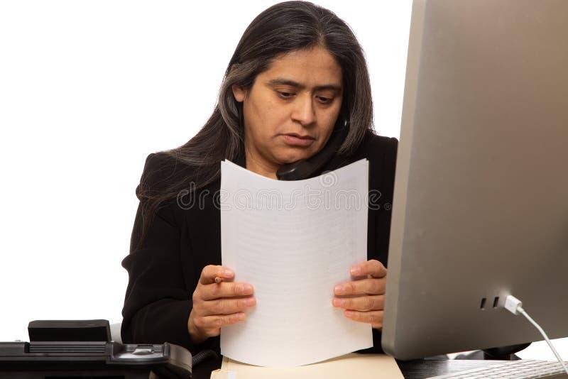 Mulher de negócios latino-americano Organizing Paperwork While que fala no telefone imagens de stock