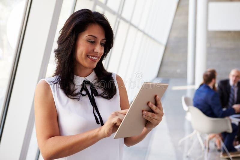 Mulher de negócios latino-americano Using Digital Tablet no escritório moderno imagem de stock royalty free