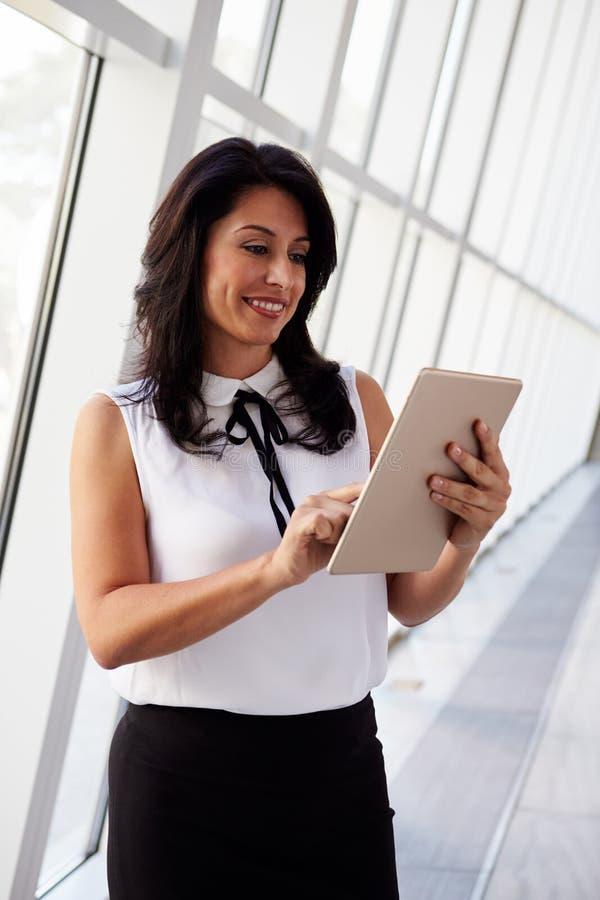 Mulher de negócios latino-americano Using Digital Tablet no escritório moderno fotografia de stock