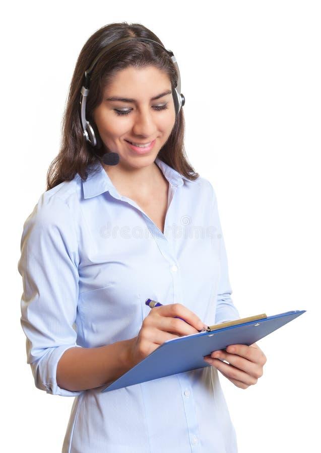 Mulher de negócios latino com notas da escrita dos auriculares foto de stock