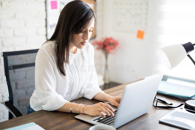 Mulher de negócios latino que trabalha em sua mesa fotografia de stock