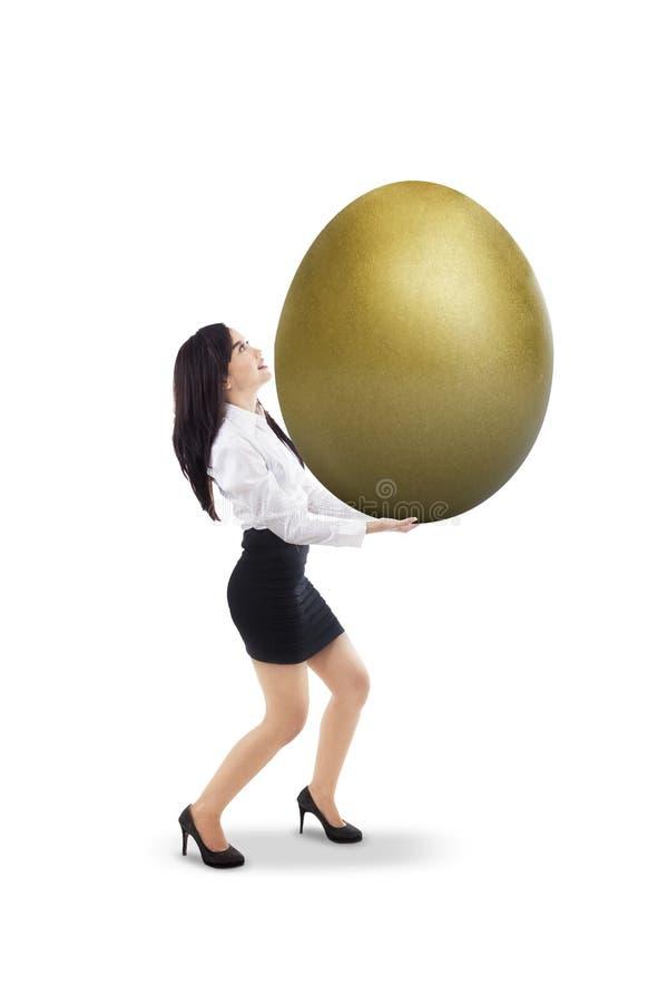 A mulher de negócios leva o ovo dourado - isolado foto de stock royalty free