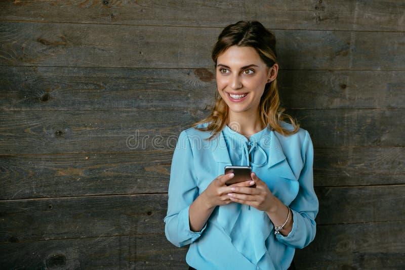 A mulher de negócios lindo guarda um smartphone que olha ao lado imagens de stock
