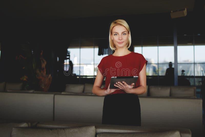 Mulher de negócios lindo nova que realiza na tabuleta digital das mãos ao estar no interior moderno do restaurante, foto de stock royalty free