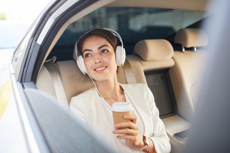 Mulher de negócios Listening à música no táxi foto de stock royalty free