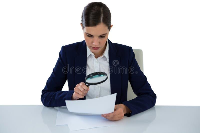 Mulher de negócios Looking At Document através da lupa fotos de stock
