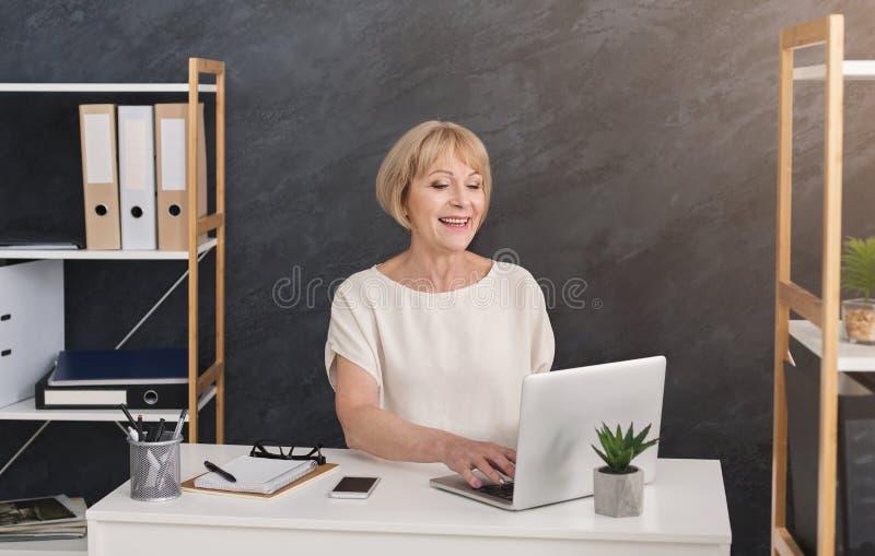 Mulher de negócios loura bem sucedida que trabalha no portátil no escritório imagens de stock