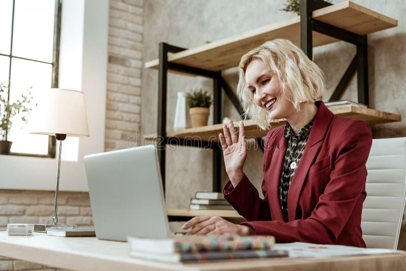 Mulher de negócios loura de cabelos curtos de irradiação no revestimento vermelho que tem a chamada em linha imagens de stock royalty free
