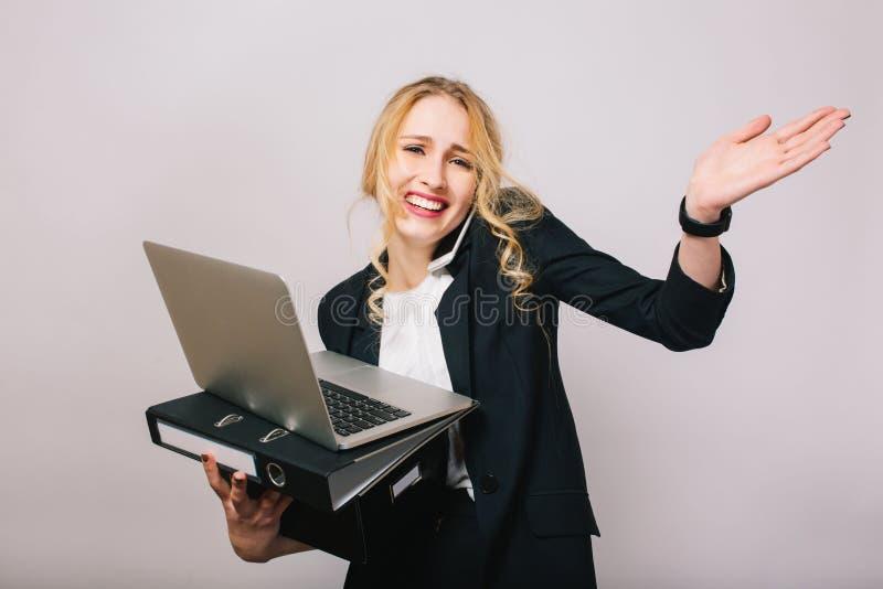 Mulher de negócios loura engraçada bonita no terno com portátil, dobrador, caixa nas mãos falando no telefone isolado no branco imagens de stock royalty free