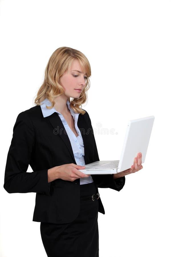 Mulher de negócios loura estada com portátil imagem de stock