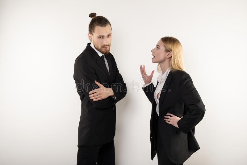 A mulher de negócios loura explica a seu sócio comercial seu ponto de vista que não quer aceitar foto de stock
