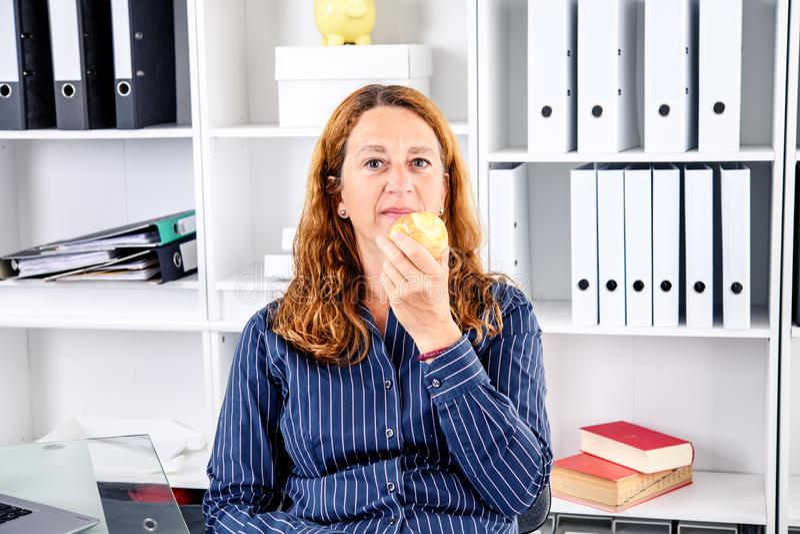Mulher de negócios loura moreno que come a maçã foto de stock royalty free