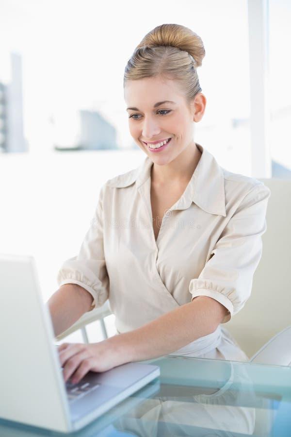 Mulher de negócios loura nova à moda que usa um portátil imagens de stock royalty free