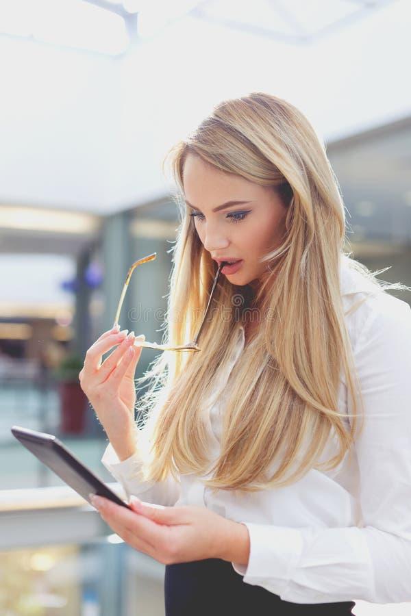 Mulher de negócios loura surpreendida por resultados financeiros ao usar a tabuleta imagem de stock