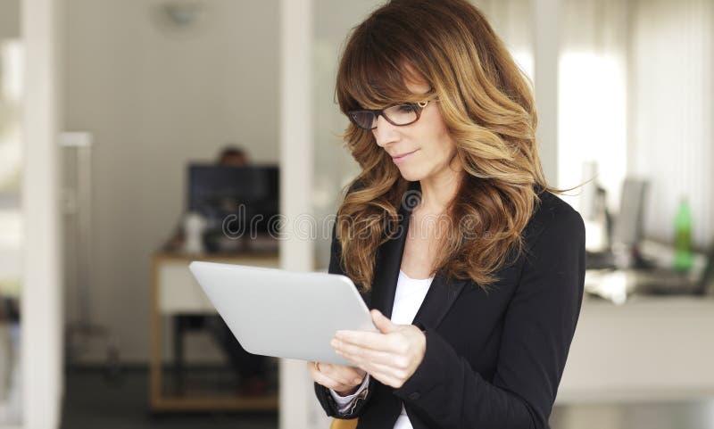Mulher de negócios madura com tabuleta de Digitas fotografia de stock