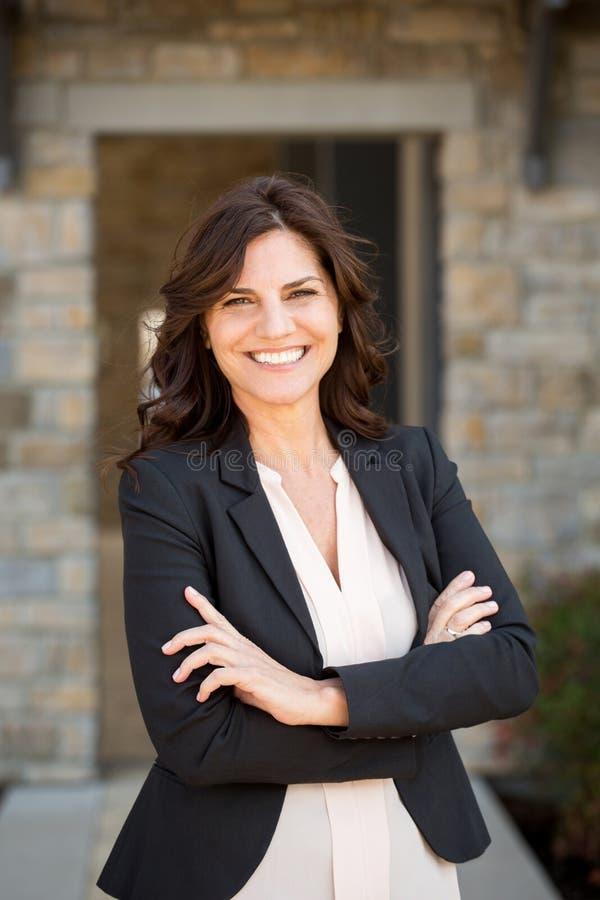 Mulher de negócios madura feliz no trabalho imagem de stock