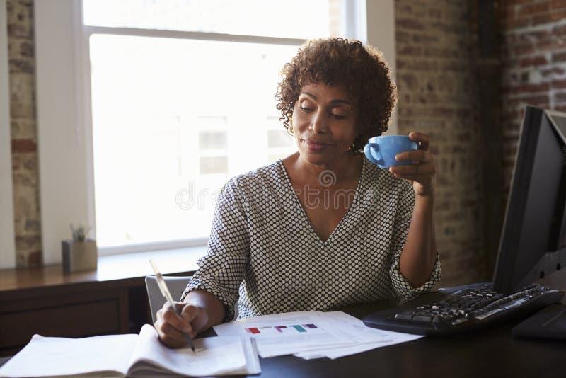 Mulher de negócios madura que trabalha no escritório foto de stock