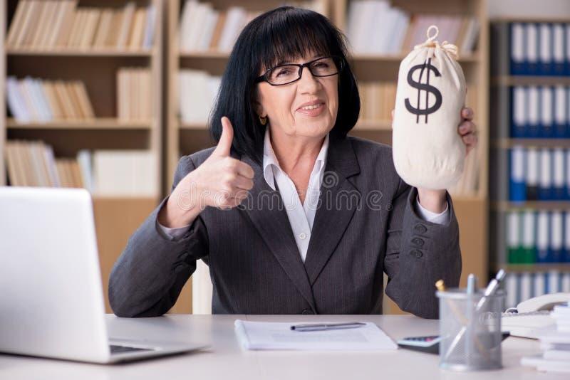 A mulher de negócios madura que trabalha no escritório fotografia de stock